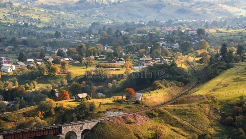 Pięknej jesieni wiejski krajobraz z pogodną doliną, małymi domami, starym wiaduktem i wijącą koleją, zdjęcia royalty free