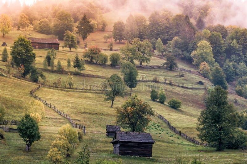 Pięknej jesieni wiejski krajobraz z starymi domami, drzewami, ogrodzeniami i mgłą, obraz royalty free