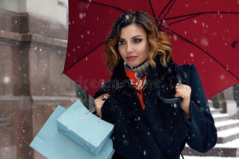 Pięknej kobiety śnieżny uliczny zakup przedstawia Bożenarodzeniowego nowego roku zdjęcie royalty free