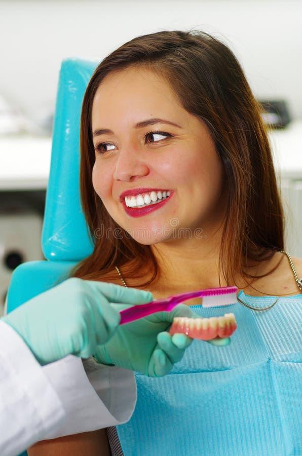 Pięknej kobiety cierpliwy ono uśmiecha się podczas gdy lekarka szczotkuje sfałszowaną stomatologiczną plakietę w dentysty ` s biu zdjęcie royalty free