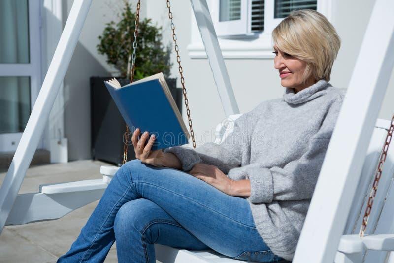 Pięknej kobiety czytelnicza książka w ganeczku obrazy stock