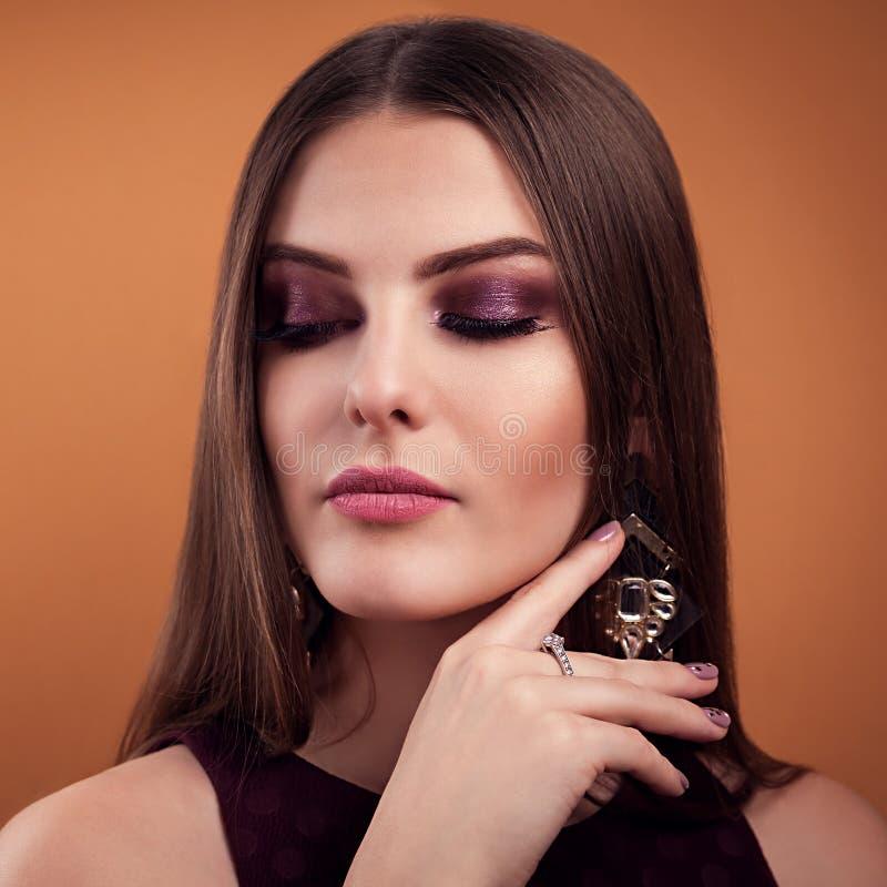 Pięknej kobiety perfect makijaż jest ubranym jewellery na brown tle obrazy stock