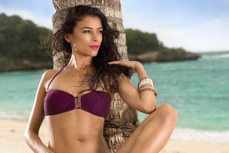 Pięknej kobiety sunbathing opierać na palmie fotografia royalty free