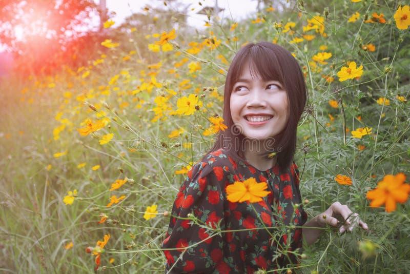 Pięknej młodej azjatykciej kobiety toothy uśmiechnięta twarz z szczęście emocji pozycją w żółtym cosmost kwiatu polu obraz royalty free