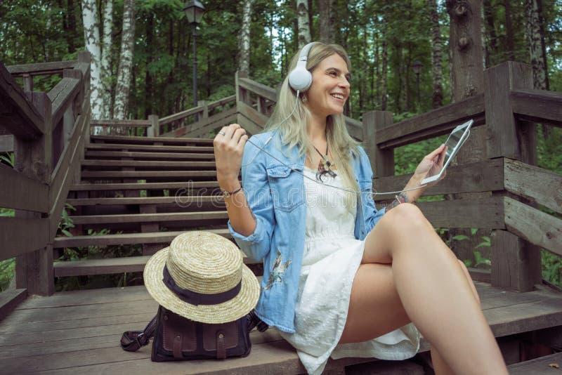 Pięknej młodej blondynka modnisia kobiety słuchająca muzyka w hełmofonach w parku z pastylką w rękach, siedzi na drewnianych krok zdjęcie royalty free