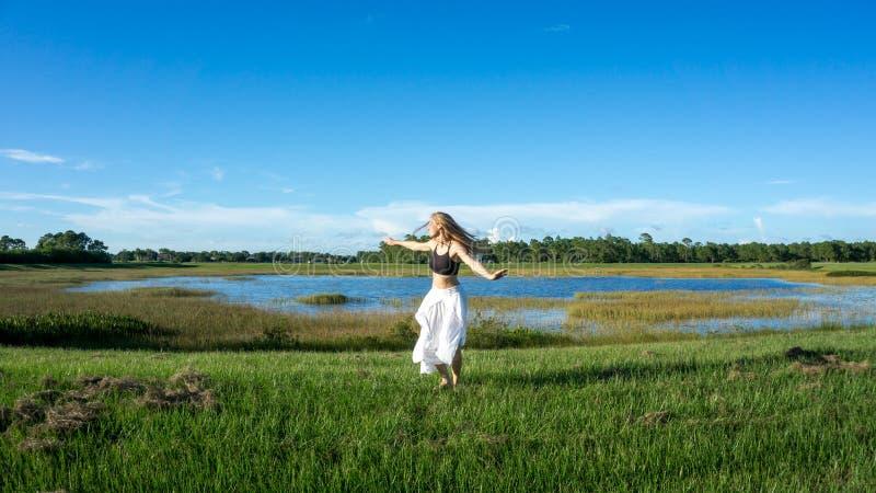 Pięknej młodej duchowej blondynki kobiety długie włosy taniec i przędzalnictwo w polu obok jeziornego bielu omijamy zdjęcia royalty free