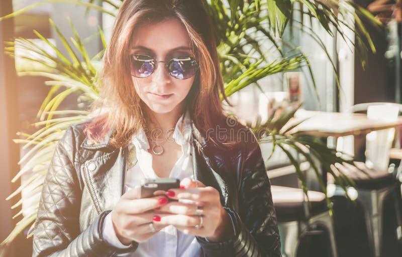 Pięknej młodej kobiety texting wiadomość na smartphone w kawiarni obrazy royalty free