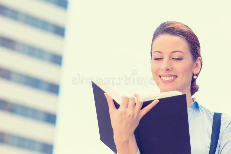 Pięknej młodej kobiety trwanie czytanie książka outdoors zdjęcie royalty free