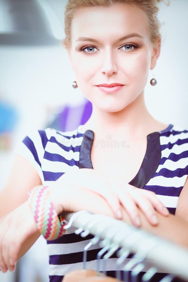 Pięknej młodej stylista kobiety pobliski stojak z wieszakami obraz royalty free