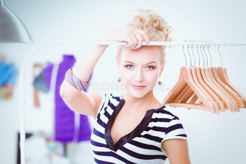 Pięknej młodej stylista kobiety pobliski stojak z wieszakami fotografia royalty free