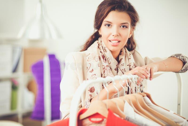 Pięknej młodej stylista kobiety pobliski stojak z wieszakami obraz stock