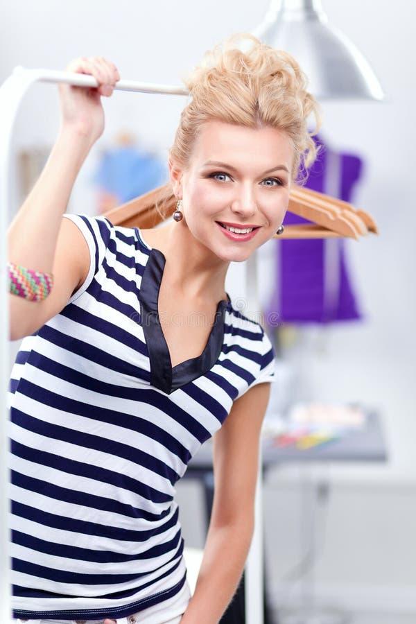 Pięknej młodej stylista kobiety pobliski stojak z wieszakami zdjęcia royalty free