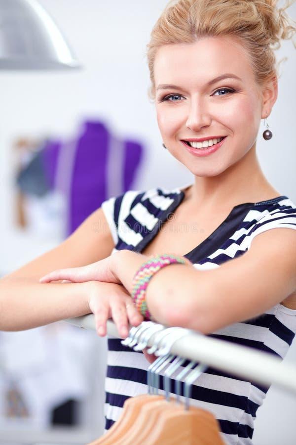 Pięknej młodej stylista kobiety pobliski stojak z wieszakami fotografia stock