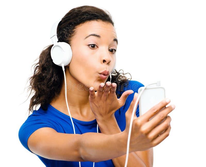 Pięknej mieszanej biegowej kobiety przesyłanie wiadomości dmuchania wideo buziak odizolowywający zdjęcia stock