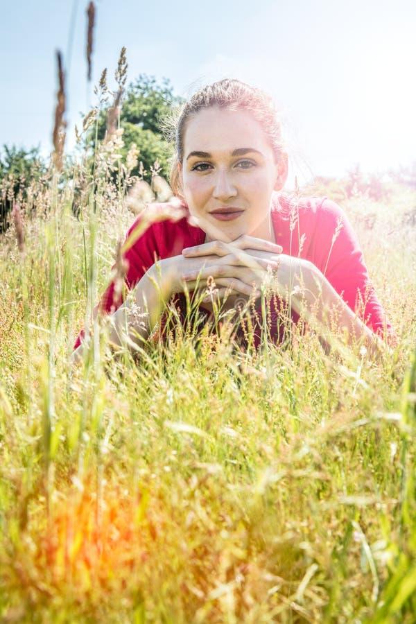 Pięknej nastoletniej dziewczyny łgarski puszek w trawie w przedpolu obrazy stock