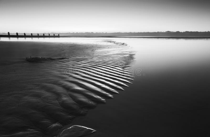 Pięknej niskiego przypływu plaży wibrujący wschód słońca w czarny i biały obrazy stock