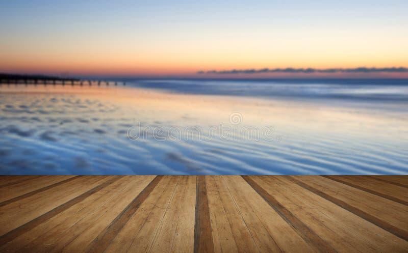 Pięknej niskiego przypływu plaży wibrujący wschód słońca z drewnianym deski floo fotografia royalty free