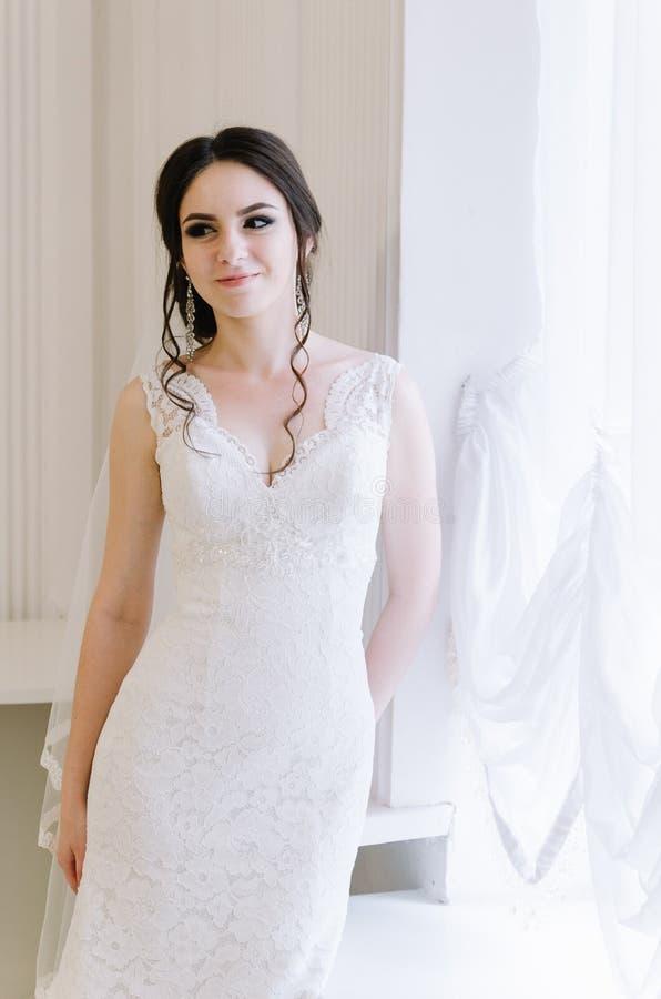 Pięknej panny młodej perfect styl Ślubny fryzura makijażu panny młodej i sukni ` s bukiet Młoda atrakcyjna panna młoda blisko okn obraz stock