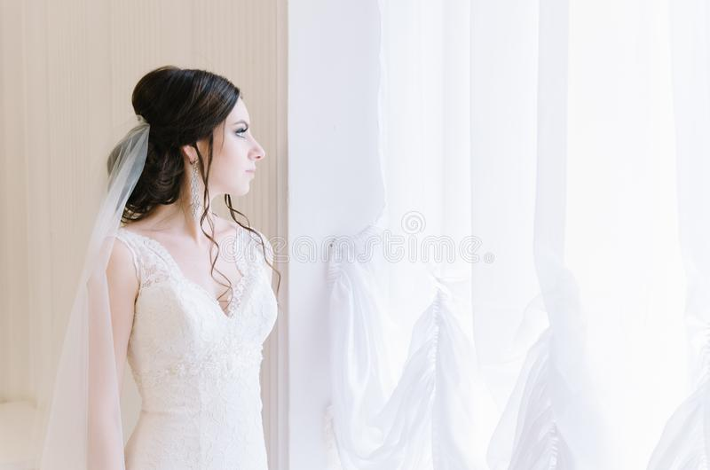 Pięknej panny młodej perfect styl Ślubny fryzura makijażu panny młodej i sukni ` s bukiet Młoda atrakcyjna panna młoda blisko okn fotografia stock