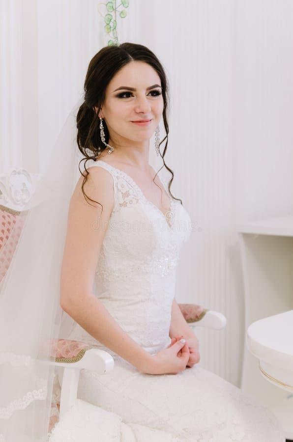 Pięknej panny młodej perfect styl Ślubny fryzura makijażu panny młodej i sukni ` s bukiet Młoda atrakcyjna panna młoda na krześle zdjęcia royalty free