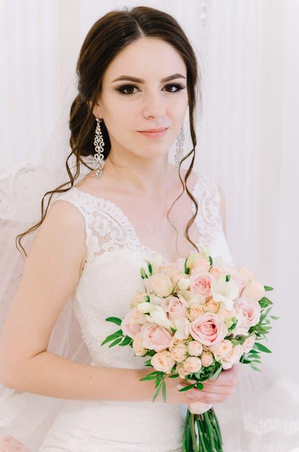Pięknej panny młodej perfect styl Ślubny fryzura makijażu panny młodej i sukni ` s bukiet Młoda atrakcyjna panna młoda na krześle zdjęcia stock