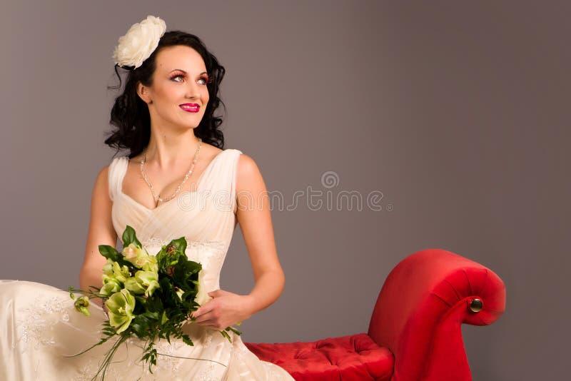 pięknej panny młodej szczęśliwa portreta czerwieni kanapa fotografia royalty free
