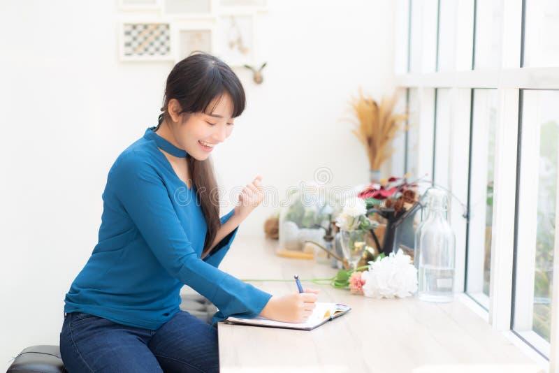 Pięknej portret azjatykciej kobiety pisarski z podnieceniem pisać na notatniku lub dzienniczku z szczęśliwym z sukcesem i uradowa zdjęcia royalty free