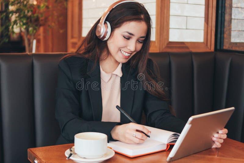 Pięknej powabnej brunetki uśmiechnięta azjatykcia dziewczyna w hełmofonach z pastylką w kawiarni, uczeń, freelancer Uczenie język zdjęcia stock