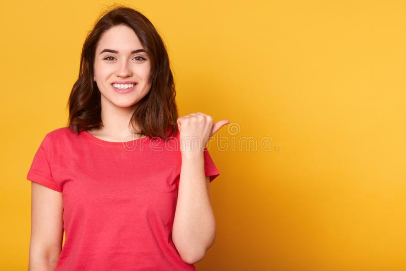 Pięknej rozochoconej brunetki żeński ono uśmiecha się szeroko przy kamerą i wskazywać kciuk oddalonego, pokazywać coś ciekawego i zdjęcie royalty free