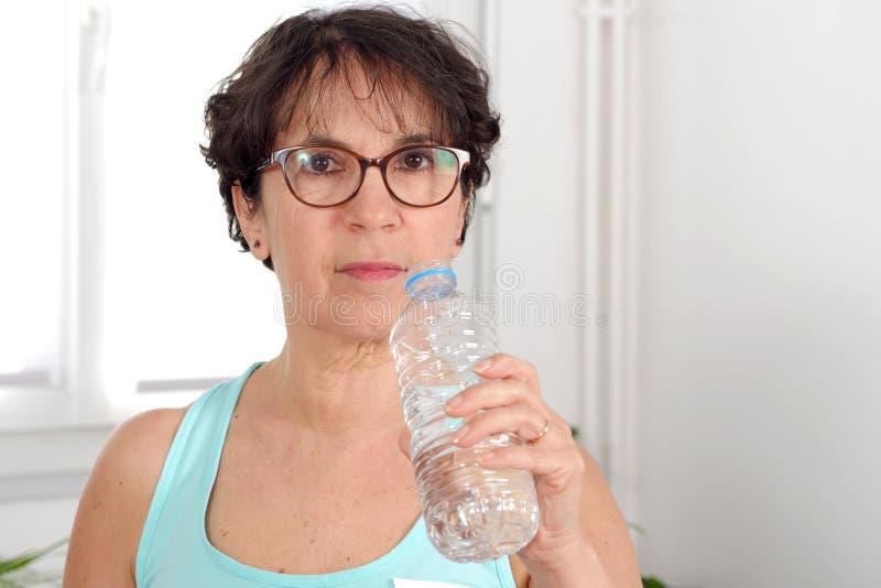Pięknej sprawności fizycznej dojrzała kobieta z bidonem zdjęcie stock