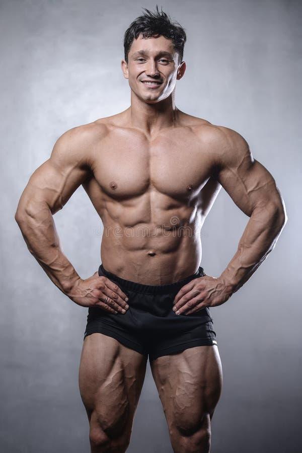 Pięknej sprawności fizycznej samiec wzorcowy pozować w studiu na bielu popielatym z powrotem zdjęcie stock