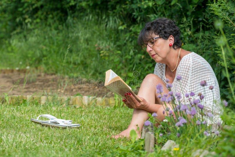 Pięknej starszej kobiety czytelnicza książka w ogródzie zdjęcie royalty free