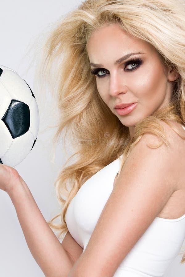 Pięknej wspaniałej płci młoda sportowa dziewczyna, blondynki kobieta ubierał w sporta ubioru mieniu i bawić się futbol zdjęcia stock