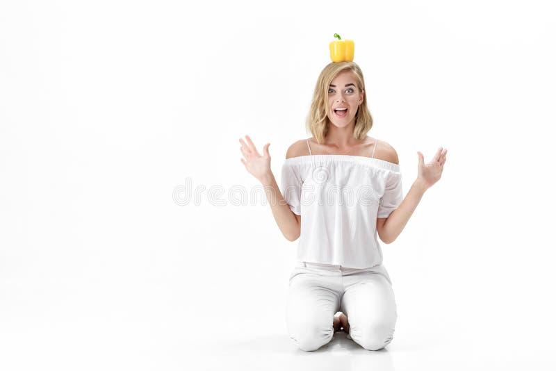 Pięknej zabawy blond kobieta trzyma żółtego dzwonkowego pieprzu w białej bluzce Zdrowa dieta i dieta fotografia royalty free