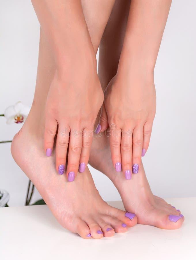 Piękni żeńscy cieki i ręki z lilym gwoździa połyskiem barwią fotografia stock