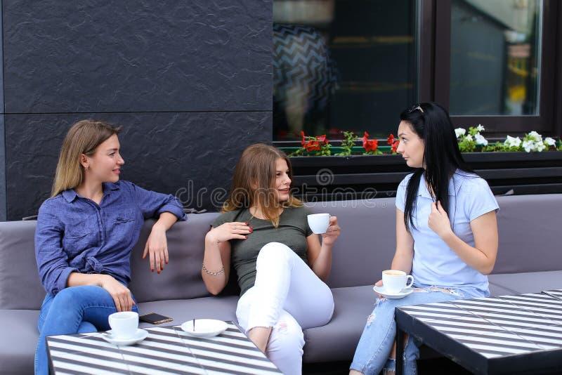 Piękni żeńscy przyjaciele śmia się i opowiada przy kawiarnią, pije kawę zdjęcia royalty free