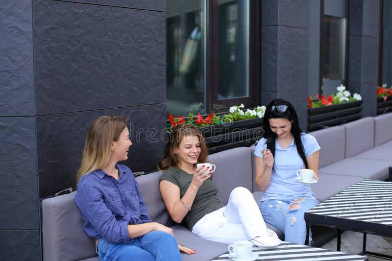 Piękni żeńscy przyjaciele śmia się przy kawiarnią i babiarstwem pije kawę, fotografia stock
