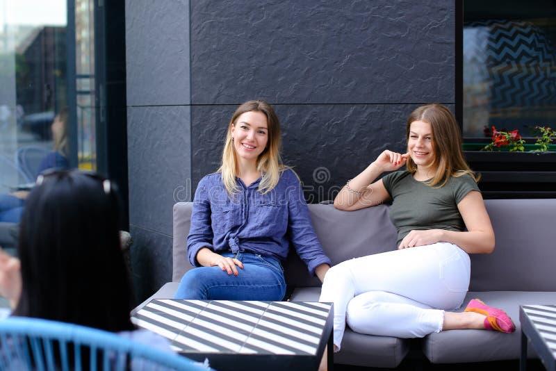 Piękni żeńscy przyjaciele opowiada przy kawiarnią i obsiadaniem na kanapie blisko okno z kwiatami zdjęcie stock