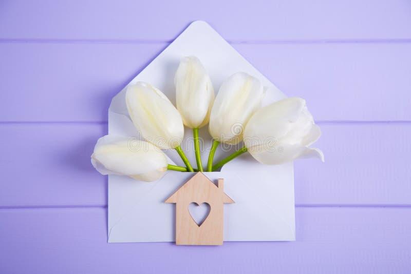 Piękni biali tulipany w kopercie z drewnianą ikoną dom z dziurą w formie serce na lilym drewnianym tle zdjęcia royalty free