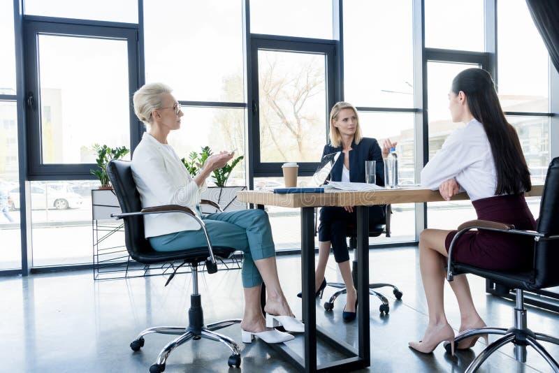 piękni bizneswomany dyskutuje i gestykuluje przy spotkaniem fotografia royalty free