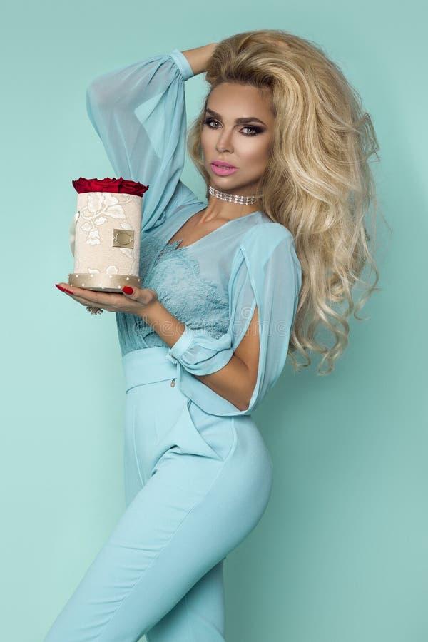 Piękni blondyny modelują w eleganckiej sukni trzyma bukiet róże, kwiatu pudełko Walentynka i urodzinowy prezent na błękitnym tle fotografia stock