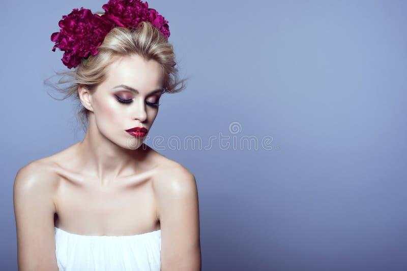 Piękni blondyny modelują z updo włosy dmuchającym wiatrem i perfect uzupełniał będący ubranym białą bez ramiączek sukni i peoni k zdjęcie stock
