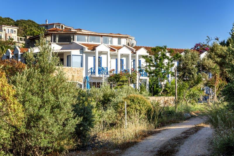 Piękni domy w zielonych drzewach wzdłuż drogi Miejscowość wypoczynkowa na słonecznym dniu obraz stock
