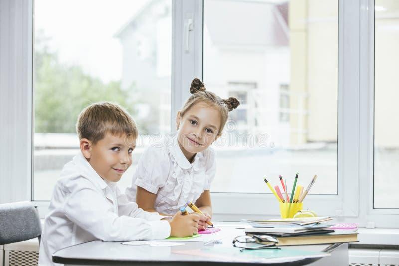 Piękni dzieci są uczniami w sala lekcyjnej wpólnie przy s zdjęcia stock