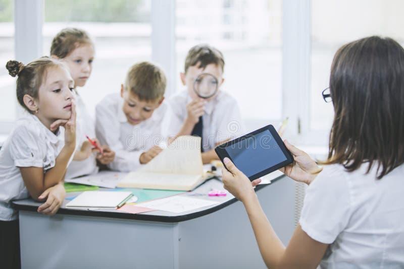 Piękni dzieci ucznie wpólnie i nauczyciel w klasie, zdjęcia stock