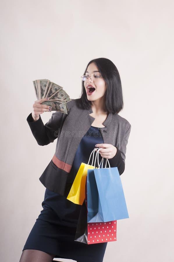 Piękni dziewczyna brasy z pieniądze i torba na zakupy rozochoconymi, trzymający obrazy royalty free