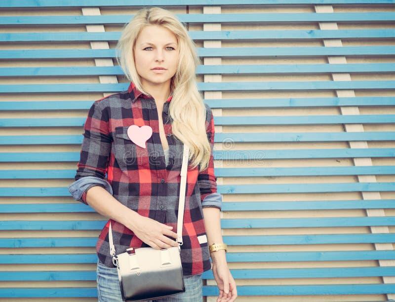 Piękni dziewczyna stojaki blisko ściany barwione drewniane deski fotografia royalty free