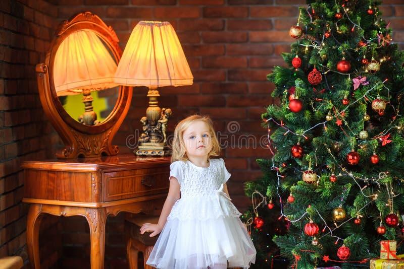 Piękni dziewczyna stojaki blisko świątecznej choinki zdjęcia stock