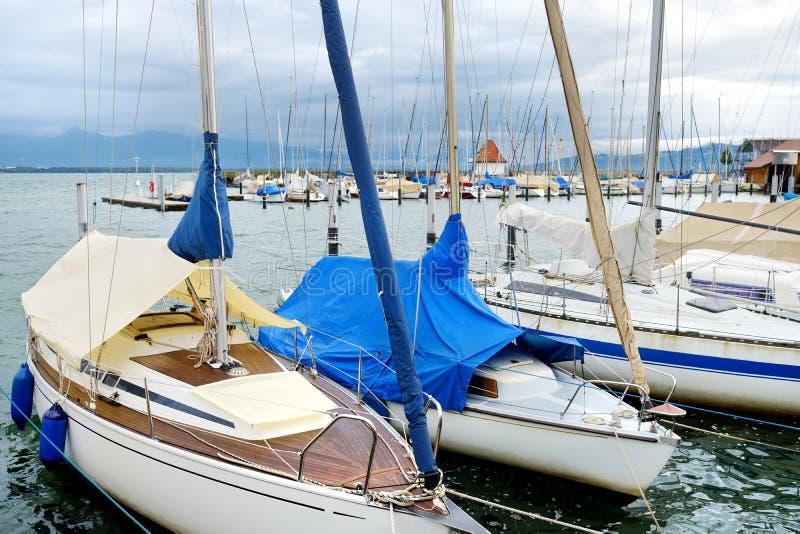 Piękni jachty w schronieniu Lindau, miasteczko na wybrzeżu Bodensee jezioro w Niemcy, na chmurnym jesień dniu obrazy royalty free