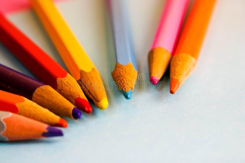 Piękni jaskrawi barwioni drewniani barwioni ostrzenie ołówki dla rysować Mieszkanie nieatutowa i odbitkowa przestrzeń na błękitny obrazy stock